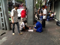 A group of men watch and enjoy a board game on the street.